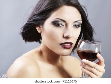 Studio portrait of a beautiful brunette holding a glass of red wine.