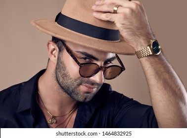 Studio portrait of a beautiful brutal tanned hipster man in a black shirt, hat and glasses
