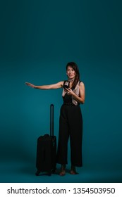 Studio portrait of a beautiful, elegant and mature Chinese Asian business woman hailing a ride she booked from her ride hailing app on her smartphone. She is standing next to her luggage.