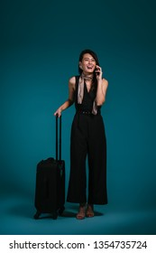 Studio portrait of a beautiful and elegant Singaporean Chinese Asian business woman in a stylish black outfit smiling as she talks on her smartphone with her travel luggage bag on wheels.
