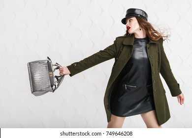 Studio portrait of beautiful fashionable woman holding silvery bag, posing on white geometric background. Model wearing stylish leather cap, short dress, green coat. Female fashion concept