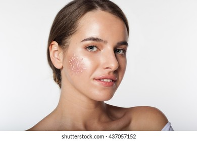 Studio portrait of beautiful girl with sunscreen cream on her face