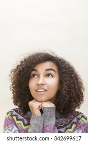 Studio portrait of beautiful happy mixed race African American girl teenager female young woman looking up thinking, dreaming or wishing