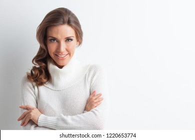 Studio portrait of beautiful long-haired woman in warm sweater on white background