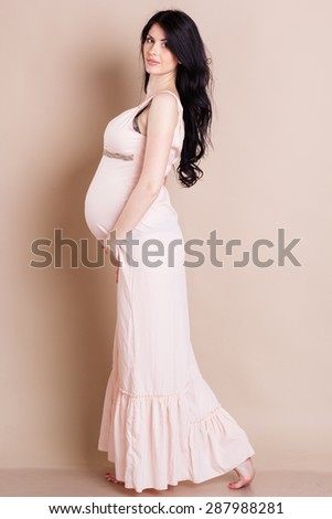 ba7e62a9e9b7e Studio portrait of beautiful pregnant woman is wearing nice long dress and  holding her belly