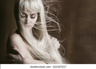 Studio portrait of beautiful sexy woman with long blonde flying hair
