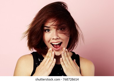 Studio portrait of beautiful surprised female with open mouth over pink background.