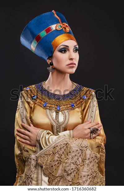 studio portrait of a beautiful woman with brown eyes and evening make-up in the image of Queen Cleopatra, crown, necklace, golden dress