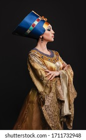 studio portrait of a beautiful woman with evening make-up in the image of Queen Cleopatra, crown, necklace, golden dress