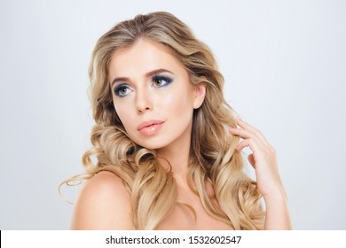 Studio Portrait of Beautiful Young Blond Woman with Long Wavy Hair and Pink Lips. Fashion Make Up and Curls Hair.