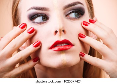Studio portrait of a beautiful young blonde girl with a bright make-up with red lipstick and nails and golden line on face. Beauty industry and face art concept. Professional model.