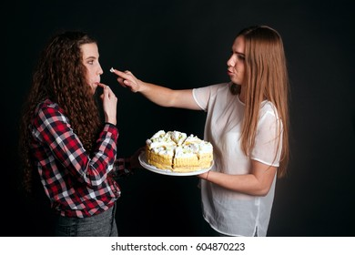studio portrait of Beautiful young caucasian women girls sisters best friends bff isolated on black background, laughing, playing the fool, act the ass goofy eating cake smearing each other with cream