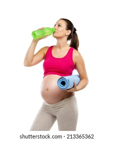 Studio portrait of a beautiful young pregnant woman holding exercising mat and drinking water, isolated on white background