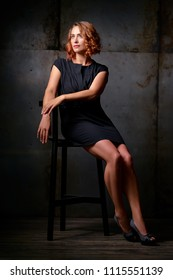 Studio Portrait of Beautiful young woman with ginger hair in little black dress against dark background.