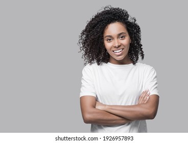 Studio portrait of a beautiful young woman with black curly hair. African american girl with crossed arms looking at camera. Isolated on grey background. People, lifestyle, beauty concept
