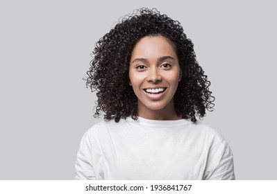 Studio portrait of a beautiful young woman with black curly hair. Laughing mixed race girl wearing white t-shirt looking at camera. Isolated on grey background. People, lifestyle, beauty concept
