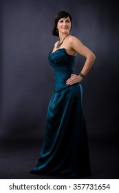 Studio portrait of beautiful young woman wearing dark blue evening dress, posing with hands on hip, smiling.