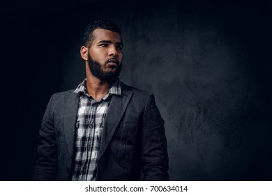 Studio portrait of Black hipster male dressed in a fleece shirt and a jacket posing over grey artistic background.