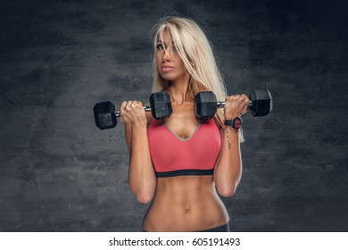 Studio portrait of blond female holds dumbbells over grey background.