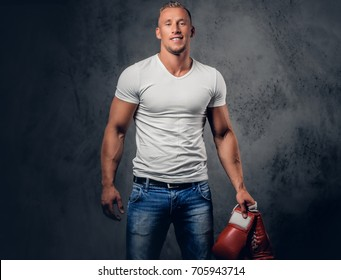 Studio portrait of blond fighter male with red boxing gloves, dresses in a white t shirt over grey background.