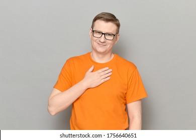 Studioporträt eines blonden, reifen Mannes mit hellem T-Shirt, Lächeln, Kamera ansehen, Hand auf der Brust halten, jemandem danken, Dankbarkeit und Wertschätzung ausdrücken, auf grauem Hintergrund stehen