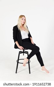 Studio portrait of blonde girl in full growth isolated on white background. Beautiful girl is sitting on a chair.