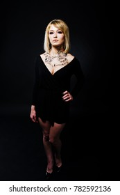 Studio portrait of blonde girl with originally make up on neck, wear on black dress at dark background.