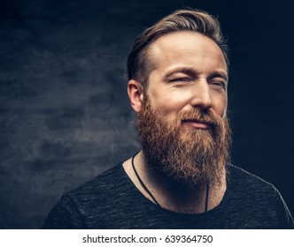Studio portrait of blue eyed redhead bearded hipster male on grey background.