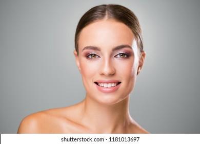 Studio portrait of brunette beauty in feminine makeup.