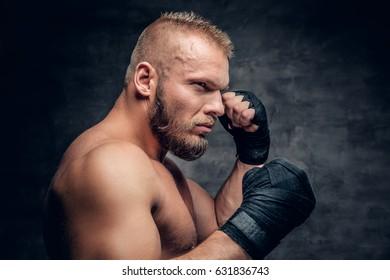 Studio portrait of brutal bearded fighter over dark grey background.