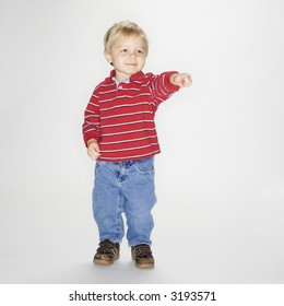 Studio portrait of Caucasian boy standing and pointing against white background.