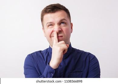 studio portrait caucasian man finger in nose. Concept of impolite