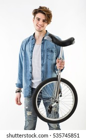 Studio portrait of caucasian young man standing up on white background holding a unicycle on his left man. fashion guy latin lover