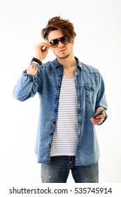 Studio portrait of caucasian young man standing up while keeping his sunglasses with right hand and hoolding the smartphone on the left. fashion guy latin lover on white background