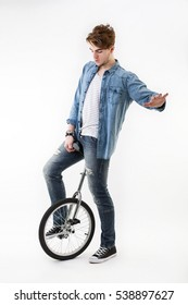 Studio portrait of caucasian young man keeping one's balancestanding up on his unicycle. fashion guy latin lover on white background