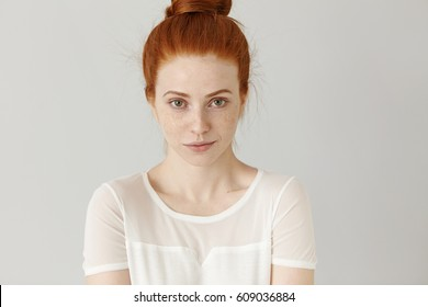 Studio portrait of charming young redhead woman with hair bun standing against white blank wall background with copy space for your text or advertising content, staring at camera with sly look