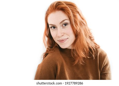 Studio portrait of cheerful red haired young woman