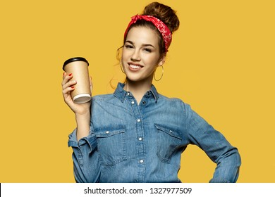 Studio portrait of cheerful sweet lady posing with tied up hair and looking at camera with pleasure. Lovely young woman holding hot coffee on yellow background. Lifestyle concept