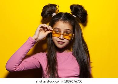 Studio portrait of cheerful teenage girl with glasses on yellow background.