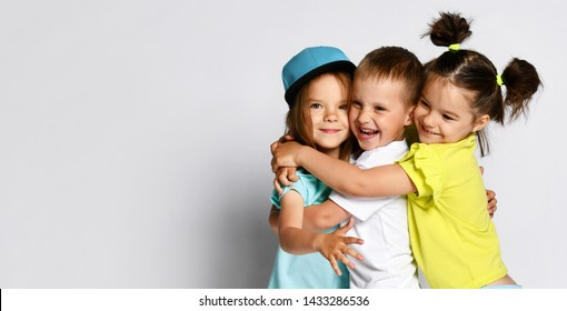 Studio portrait of children on a light background: full body shot of three children in bright clothes, two girls and one boy. Triplets, brother and sisters. hugging on camera. Family ties, friendship.