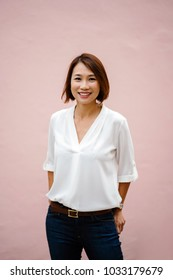 Studio portrait of a Chinese Asian woman against a plain pink background. She is dressed in an elegant white blouse and jeans (smart casual) with a bob and is smiling.