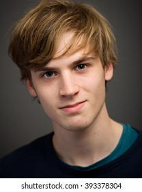 Studio portrait of a confident blond teenage young man with half long hair isolated against a grey background.