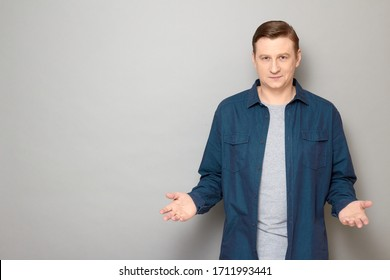 Studio portrait of confident friendly man wearing shirt, smiling, stretching hands, offering product, inviting to discussion, waiting your decision, standing over gray background, copy space on left