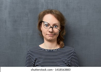 Studio portrait of confused caucasian fair-haired young woman with skewed glasses, wearing striped blouse, making clueless and silly face, looking with incomprehension at camera, over gray background