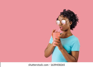 Studio portrait of a cool young woman with sunglasses,  drinking from glass with straw