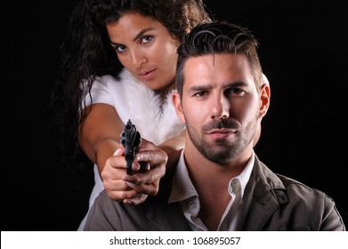 studio portrait of a couple of criminals or detectives with a gun