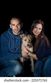 studio portrait of a couple and their cute adopted half breed dog