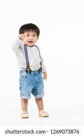 Studio portrait of cute, adorable, Asian toddler boy wearing denim overalls, long sleeve T-shirt, orange shoes, standing, smiling broadly, on isolated white background