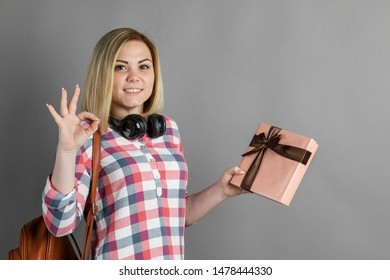 Studio portrait of a cute blond girl, a student, in a plaid shirt looking at a gift / a pleasant surprise, a gift in a box, joyful jubilation, Valentine's Day.