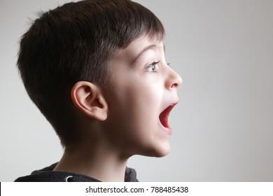 Studio portrait of cute boy screaming - side view